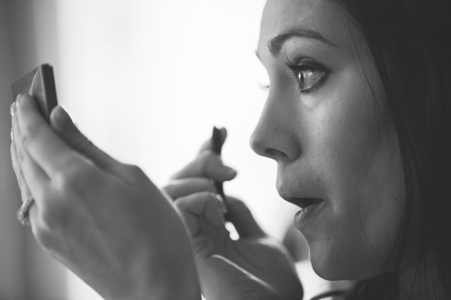 Bride applies makeup in the double tree hotel omaha