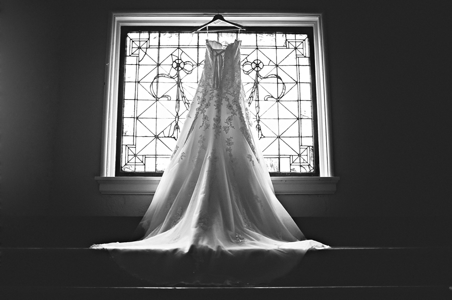 Wedding Dress Hanging By Stained Glass Window