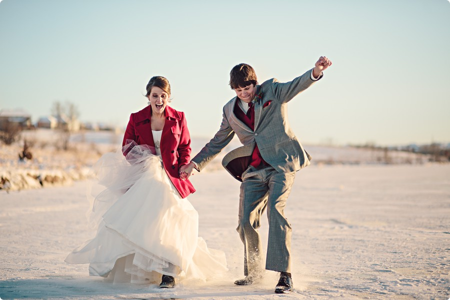 Bride and Groom sliding on a frozen lake in Omaha